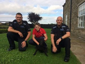 Flash the hero Patterdale Terrier with his owners and police officer